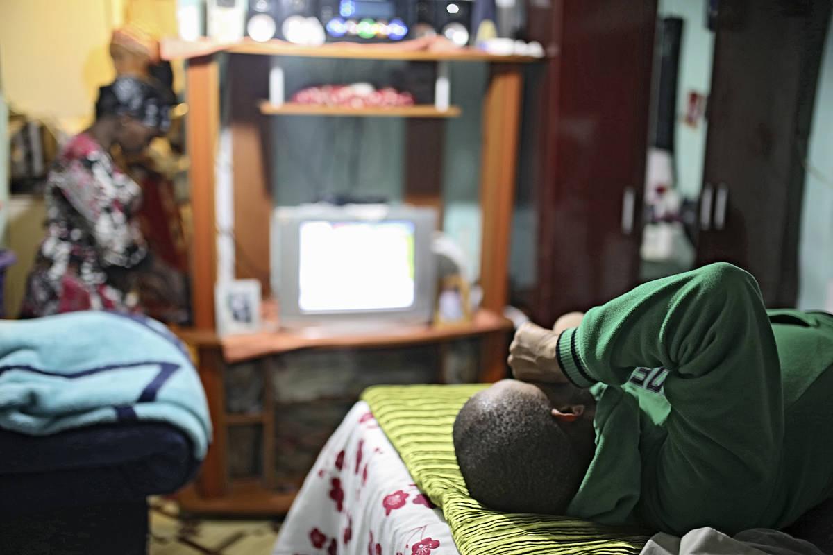 mies katsoo makuultaan televisiota