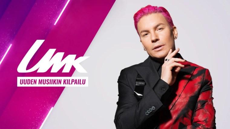 Pinkkitukkainen Antti Tuisku seisoo vaalean taustan edessä toinen käsi leukaa hipaisten, vieressä UMK-grafiikat.