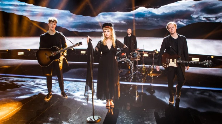 Haloo Helsinki!  The band poses seriously dressed in black on the UMK stage.  Elli has a pillow hat and a black veil resembling a funeral outfit.