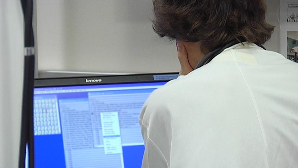 Lääkäri katsomassa potilastietoja tietokoneelta.