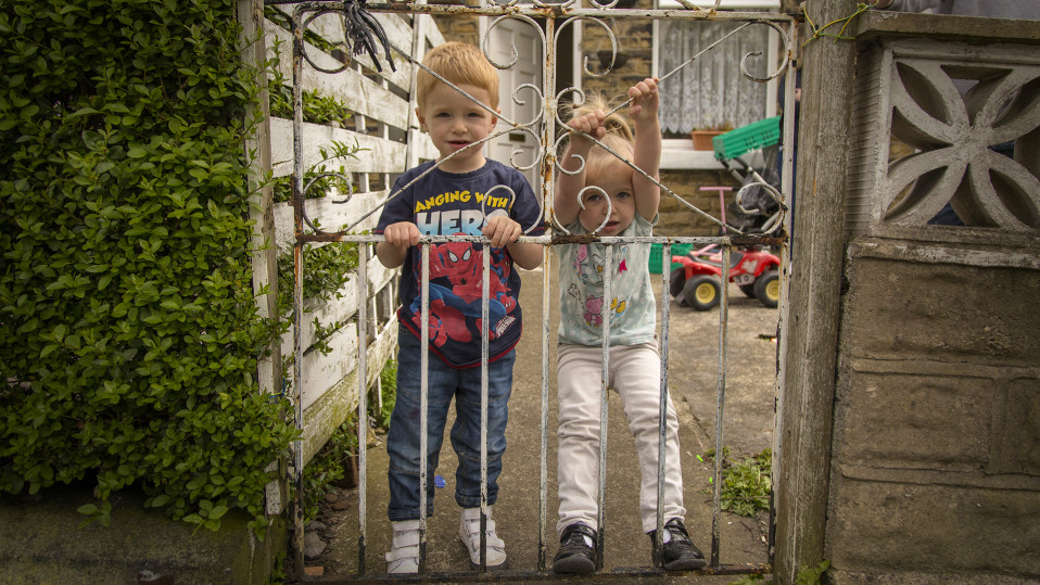 Kaksi pientä punertavatukkaista lasta roikkuu ruosteisessa rautaportissa.