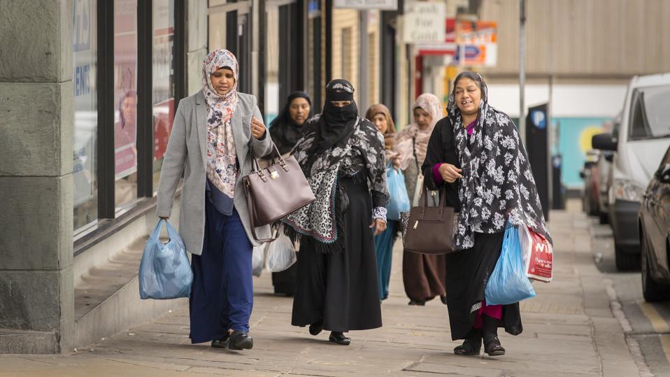 Islamilaisiin päähuiveihin pukeutuneita naisia kadulla. Keskimmäinen nainen on verhonnut myös kasvonsa mustalla huivilla.