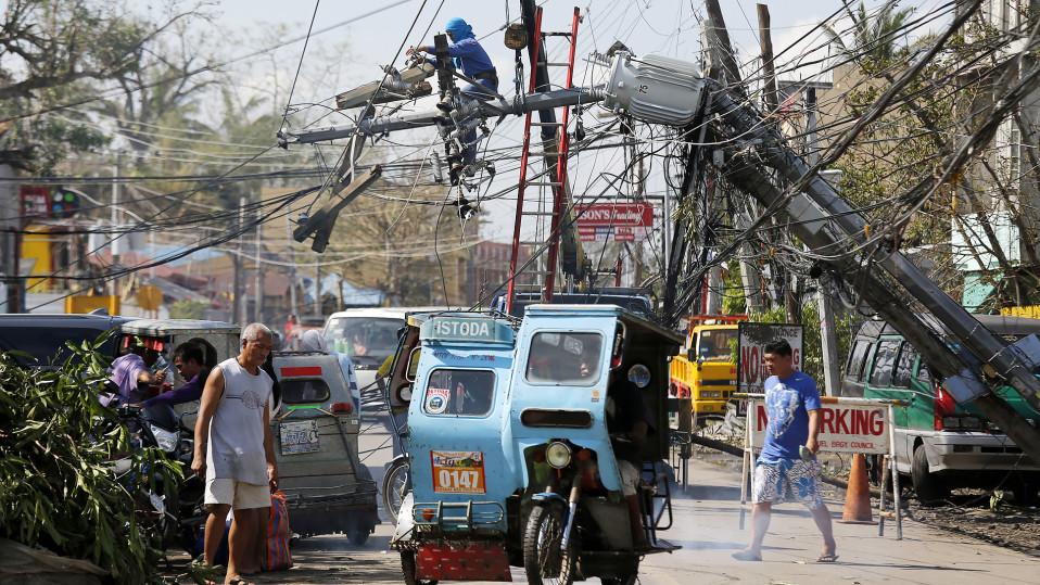 Mies korjaa Taifuuni Nock-Tenin aiheuttamia tuhoja Filippiineillä.
