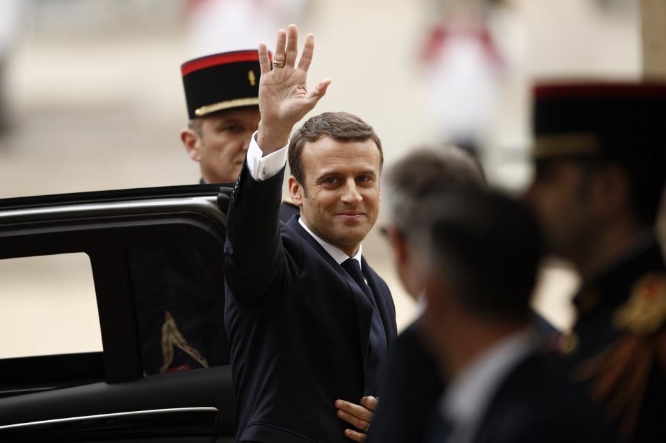 Emmanuel Macron astuu ulos autosta ja tervehtii kohti kameraa.