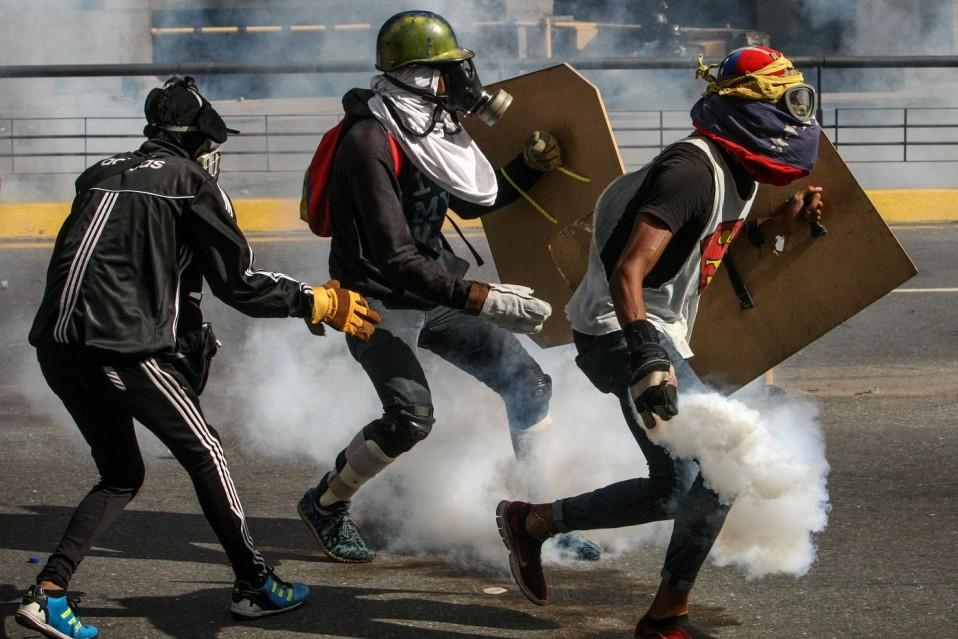 Kolme kypäräpäistä ja kaasunaamerein varustautunutta mielenosoittajaa.
