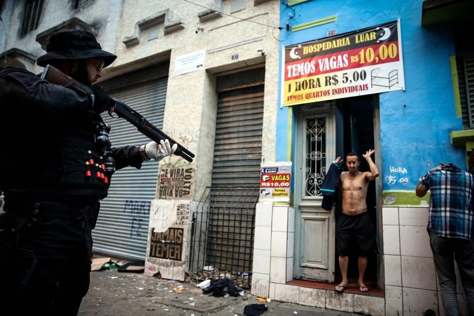 Oviaukossa mies kädet ylhäällä musta pukuinen mies osoittaa häntä aseella.