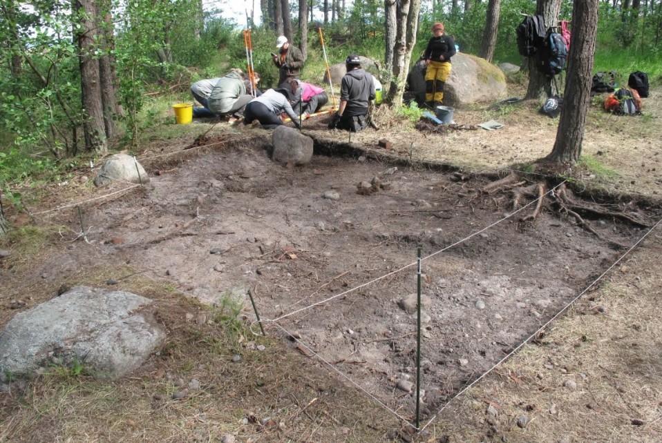 Kaivajia neliönmuotoisen kaivuualueen vieressä. Maan pintakerros on poistettu.