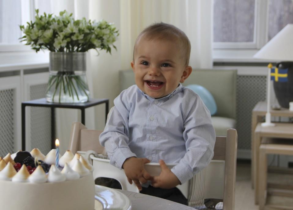 Oscar hymyilee syöttötuolissa, edessä kakku, jossa yksi kynttilä.