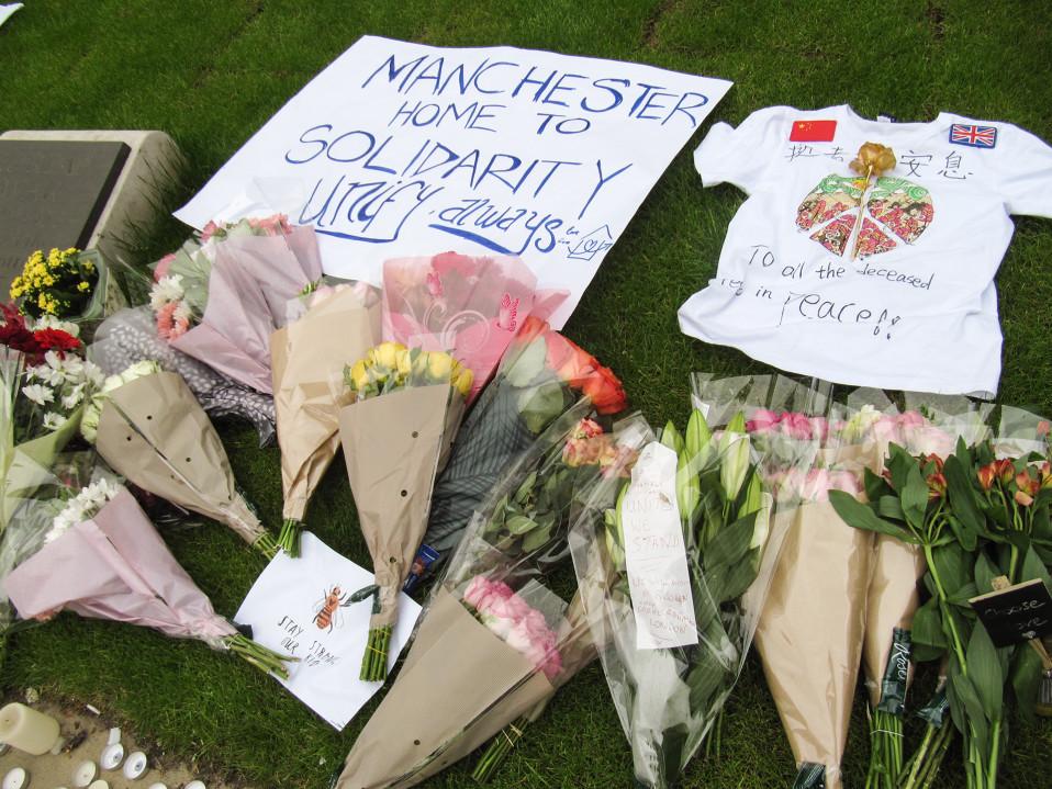 Nurmelle on asetettu kukkia, tee-paita, jossa rauhanmerkki, sekä kyltti, jossa teksti