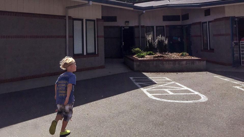 Poika juoksee koulun pihalla.