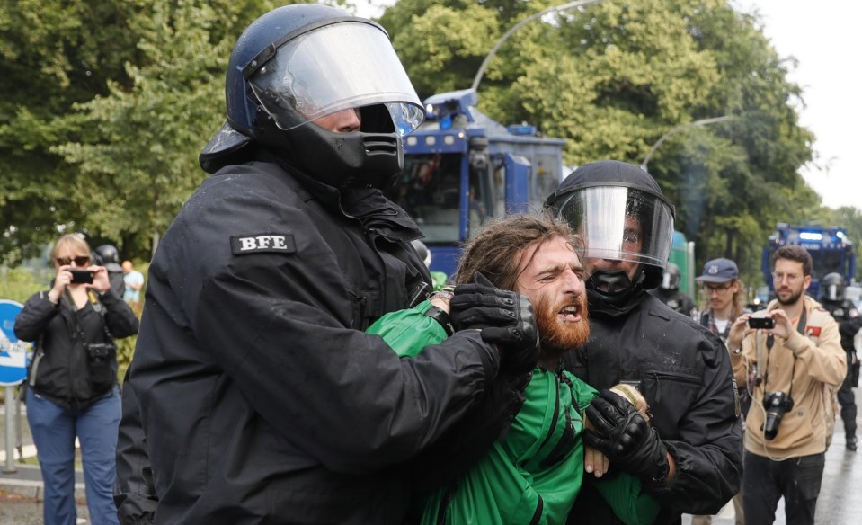 Kaksi poliisia raahaa rastatukkaista mielenosoittajaa.