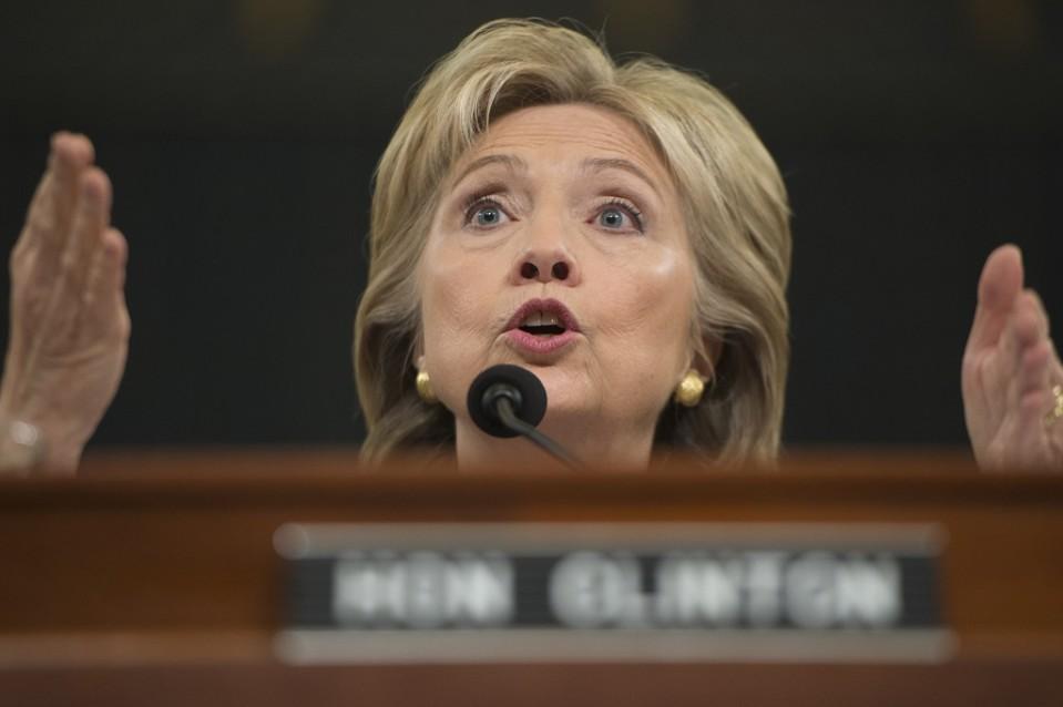 Hillary Clinton puhuu mikrofoniin ja tehostaa puhetta käsillään. Tausta on tumma. Edustalla näkyy häimeänä hänen nimikylttinsä.