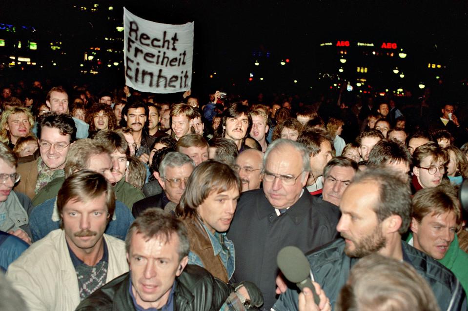 Liittokansleri Helmut Kohl (keskellä) mukana länsi- ja itäberliiniläisten kanssa juhlimassa rajojen avautumista ja Berliinin muurin murtumista 10. marraskuuta 1989.