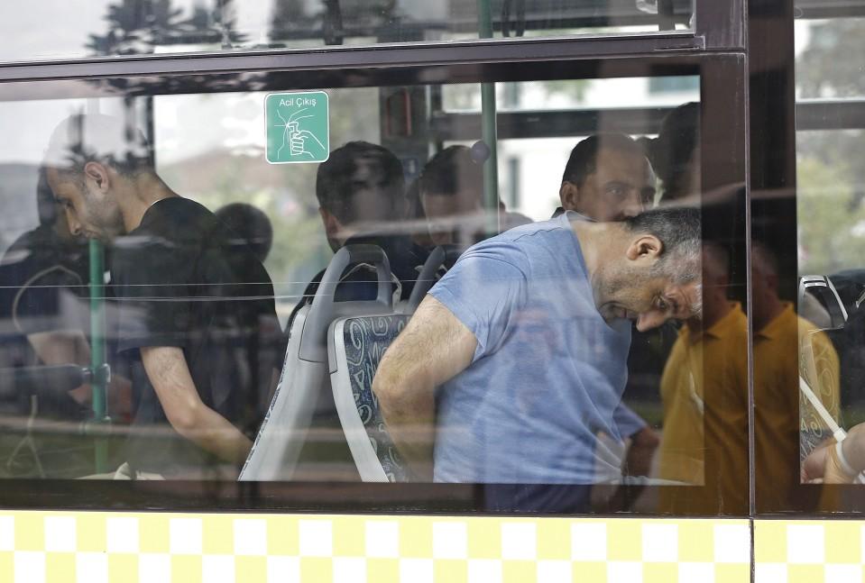 Siviilivaatteissa olevia miehiä näkyy linja-auton ikkunan läpi. Heillä on kädet selän takana.