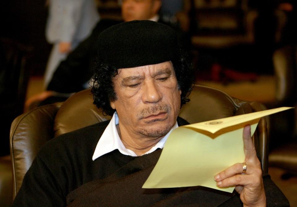 Gaddafi istuu nojatuolissa ja lukee paperia. Kyseessä on Arabiliigan kokous Damaskoksessa 2008, ja taustalla näkyy muita kokoukseen osallistujia.