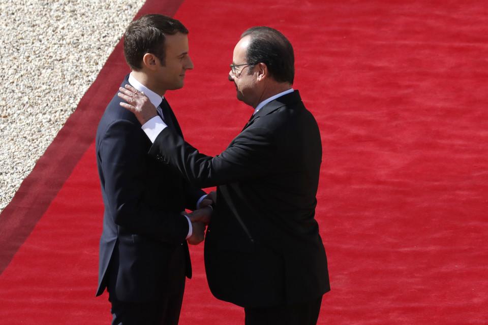 Hollande pitää kättään Macronin olalla.