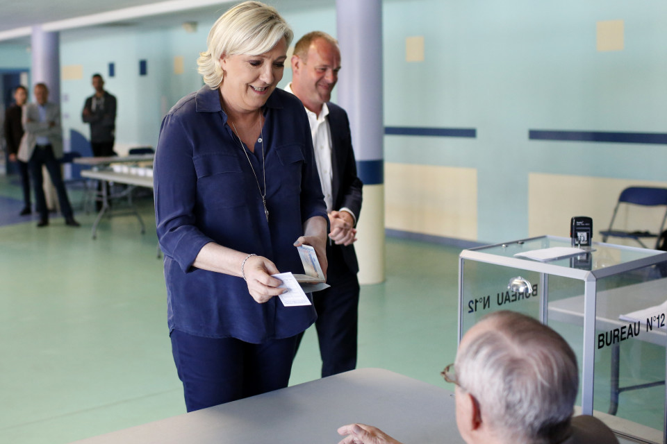 Marine Le Pen ojentaa äänestyslippua.