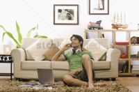 Young man talking on a mobile phone in the living room ...