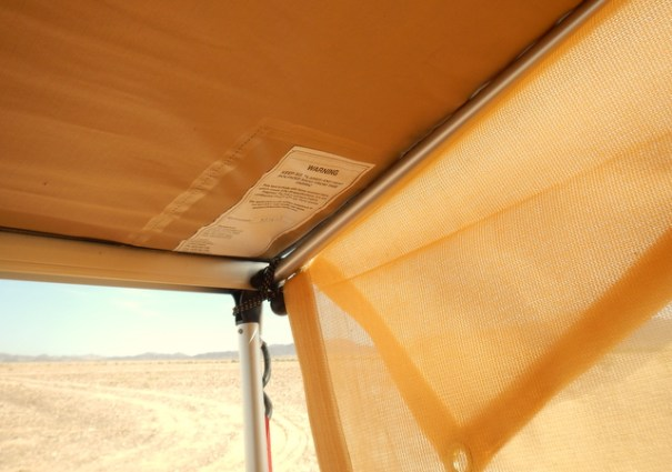 The ARB awning has extendable arms that fold out from the top and make solid sides for the awning. At the bottom of the awning it has extendable legs that fold out to become it's legs. So it is solid on all 4 sides.