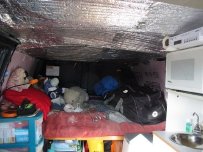 Looking toward the back of her van we see the reflectix she is using as insulation. Notice also the duffell bag she is using as organization. Again, that is a simple cheap solution to storage.