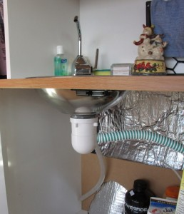 Here we see under the sink. She has a manual water pump that goes down into 5 gallon jug to give her running water in her sink. The sink drains into either another 5 gallon jug or straight out onto the ground.