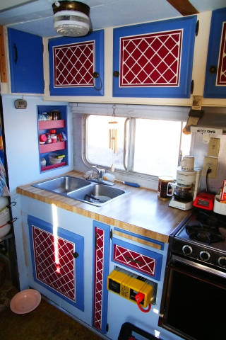 This is the kitchen of a friends Class C. He wanted it to look like home so he painted all the cabinets in cheery colors he liked, making it very homey!