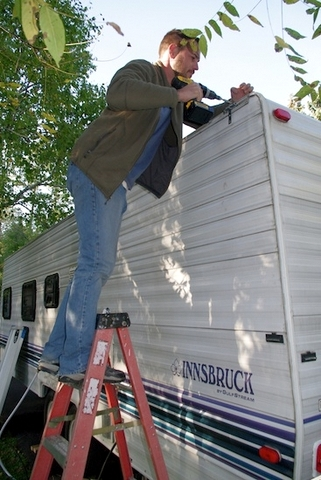 Doug's son helping him with installing the solar mounts. If he had taken a ladder with him when he bought the RV, he would have known he couldn't mount the panels on the roof! Lesson learned!