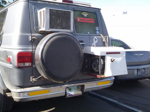 Here you see a window air conditioner mounted in the back window of a van. Notice also the generator mounted on the door to power the air conditioner. The best choice is a Honda or Yamaha 2000 (the 1000 is too small), but they are expensive.)