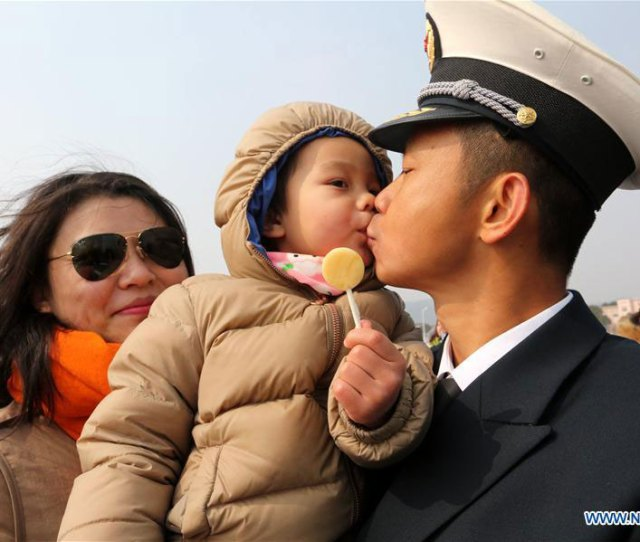 A Naval Officer Kisses His Child As He Gets Off Board In A Military Port In