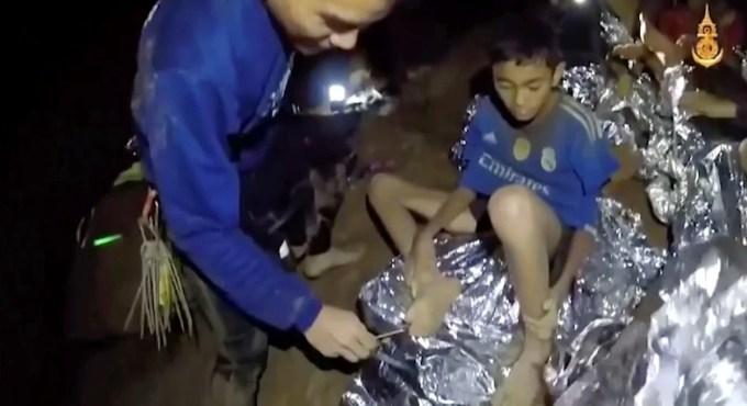 Los niñosjunto a los médicos de la Marina Tailandesa  que los ayuda a curar los heridos dentro de una cueva en Mae Sai, al norte de Tailandia. (AP)