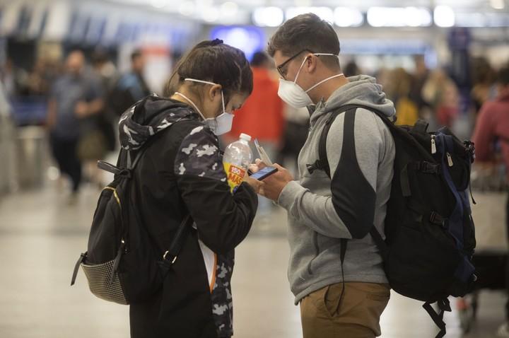 Mediados de marzo 2020: una pareja con barbijo en el Aeroparque Jorge Newbery. Foto: Xinhua/Martín Zabala