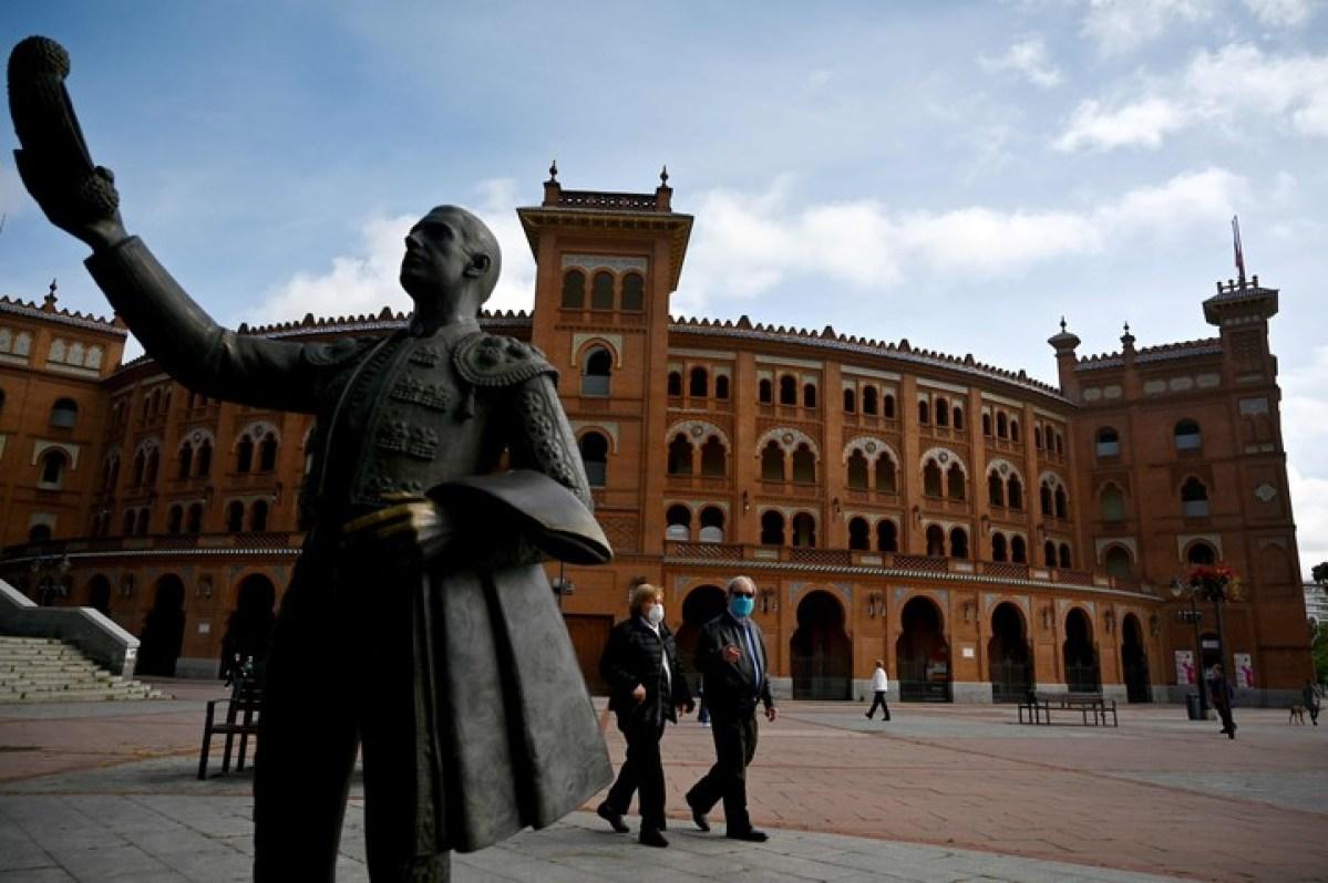 Una pareja camina por la Plaza de Toros Las Ventas, en Madrid, este sábado, en el primer día de una apertura progresiva del confinamiento. /AFP
