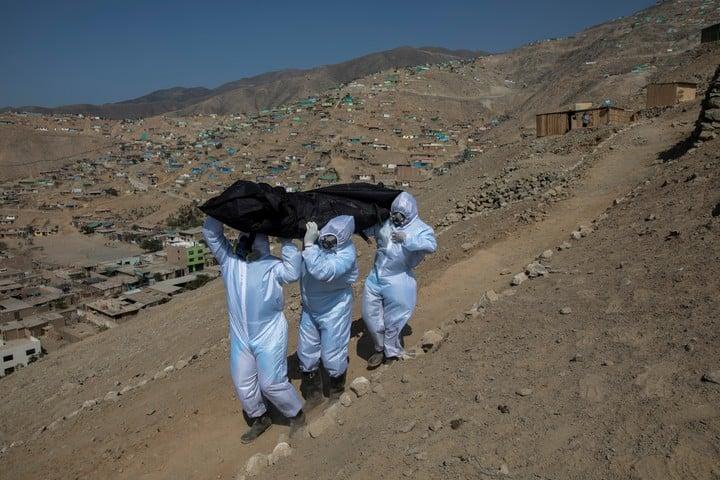 Luis Zerpa, Luis Brito y Jhoan Faneite cargan un cuerpo montaña abajo, desde un barrio marginal en Lima. / AP