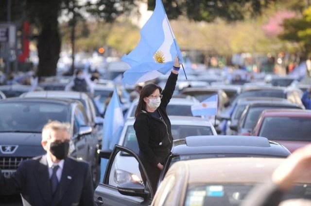 Una mujer con bandera argentina en alto, durante la protesta frente al Obelisco. Foto Martín Bonetto.