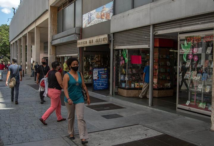 Personas portan mascarillas frente a comercios reabieros, en Caracas. Foto: Xinhua