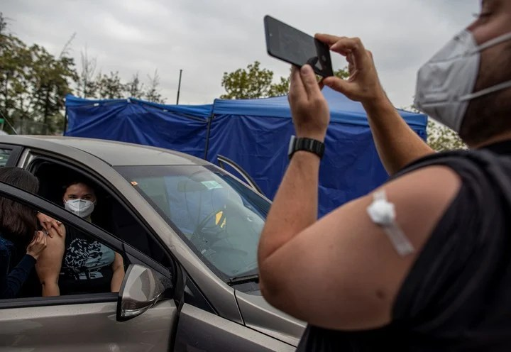 A man takes a photo after being vaccinated against Covid 19 in the National State of Santiago de Chile, in an image from March.  Photo: AP