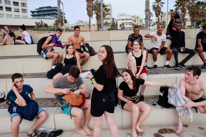 Los adolescentes ya se reúnen  sin mascarilla en la ciudad costera israelí de Tel AViv. Foto: AFP