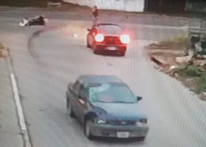 The Ford Ortion, with a visible bump from the impact, drives away leaving behind the downed motorcycle and its driver.