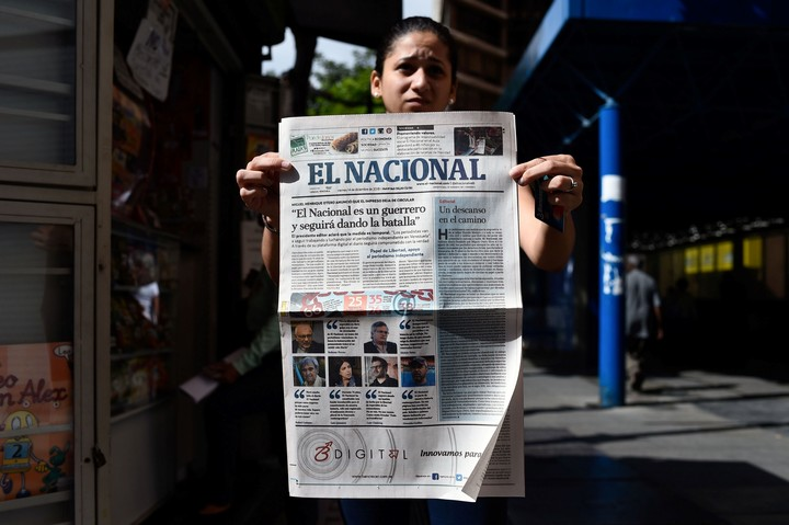 A woman shows the last cover of the Caracas newspaper El Nacional, in December 2018, before they had to close the paper edition.  Photo: AFP