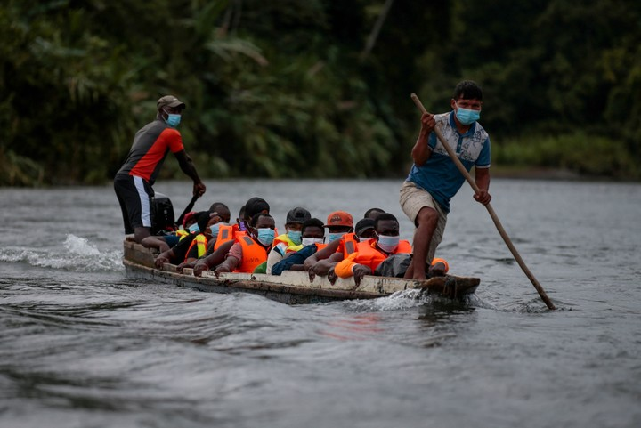 Migrants cross the Tuquesa River in precarious boats to reach Panama and continue their journey to the US Photo: AFP