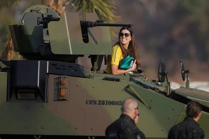 Una seguidora del presidente se sube a una vehículo armado del ejército, en Brasilia. Foto: Reuters