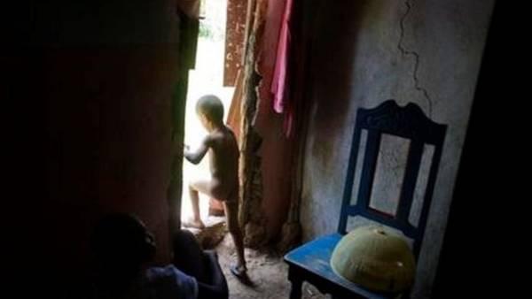 Anderson Joseph, de cinco años, sale de su casa para vestirse mientras su abuela, incapacitada, está sentada en el suelo de tierra de su casa en Port Salut, Haití. (AP Foto/Dieu Nalio Chery)
