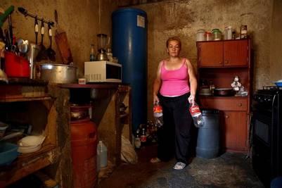 """Yunni Pérez tiene botellas de plástico que se utilizan para llevar el agua en el barrio llamado """"El Tanque"""" en la barriada de Petare en Caracas, Venezuela. (REUTERS)"""