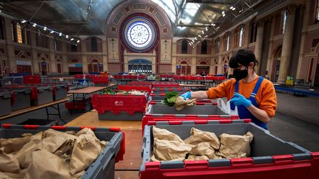 Volunteers from the Edible London Food Project help prepare food packages at Alexandra Palace in L