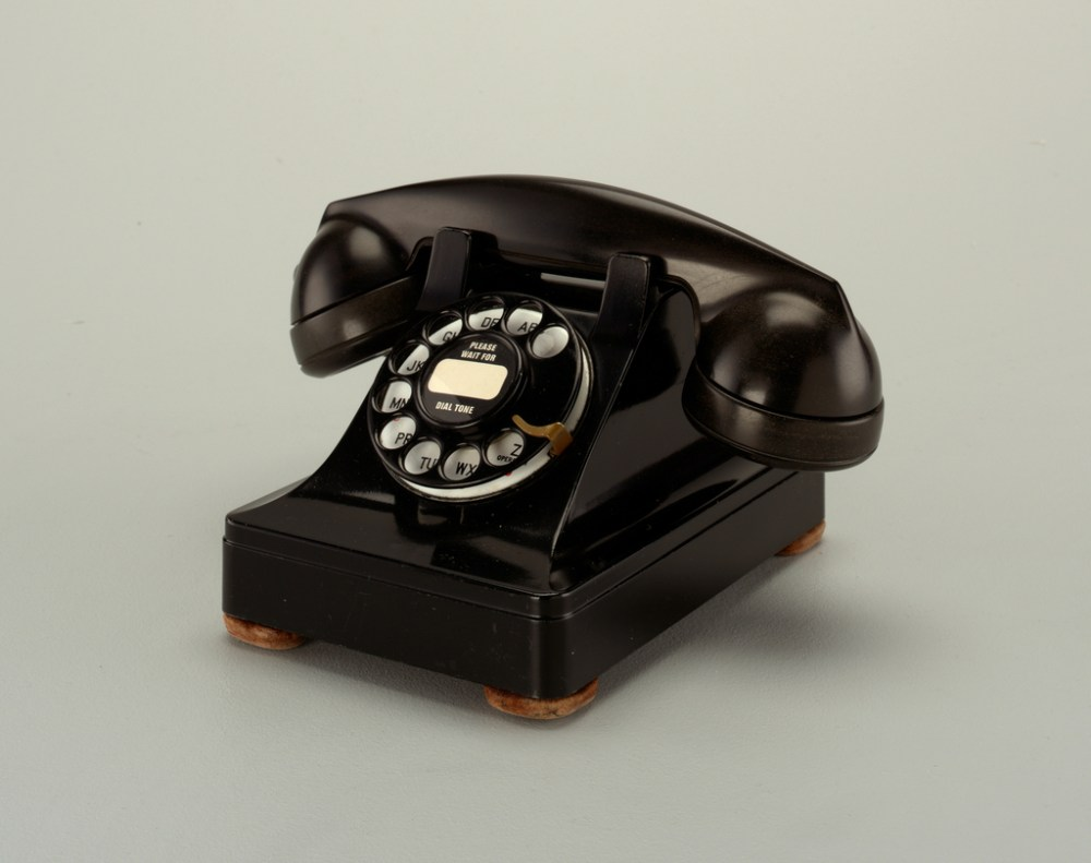 medium resolution of black rotary telephone transmitter receiver handset in cradle on raised body with square base