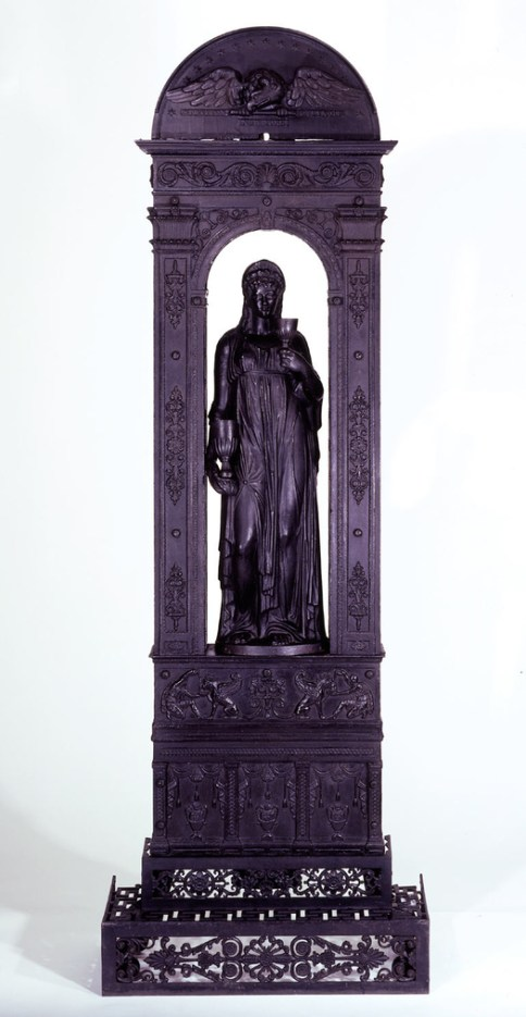 """Black cast iron radiator (b) in the form of a podium surmounted by an arch forming a niche for a standing draped figure (a) of a woman- the goddess Hebe- holding a Greek drinking goblet in either hand (d,e). A composite entablature is surmounted by a Doric cornice crowned by a semi-circular tympanum. The podium base is decorated with bas-reliefs of columns alternating with Greek vases surrounded by drapery at the lower level and repeated scene of a griffin and man pouring liquid into a bowl in the upper level. The arch itself is decorated with bas-reliefs of rosettes and scrolls on two supporting pilasters with fluted capitals. The tympanum has a bas-relief of an eagle clutching a staff from which springs ribbons bearing """"Stratton"""" and Seymour"""". Stars decorate tympanum, following the semi-circular curve. Radiator stands on four detachable scrolled legs (f/i). The fender (c) is comprised of grille work formed by scrolls, acanthus leaves and rosettes. Flat circular flue key (j) with stylized foliate handle fits on pipe behind tympanum."""