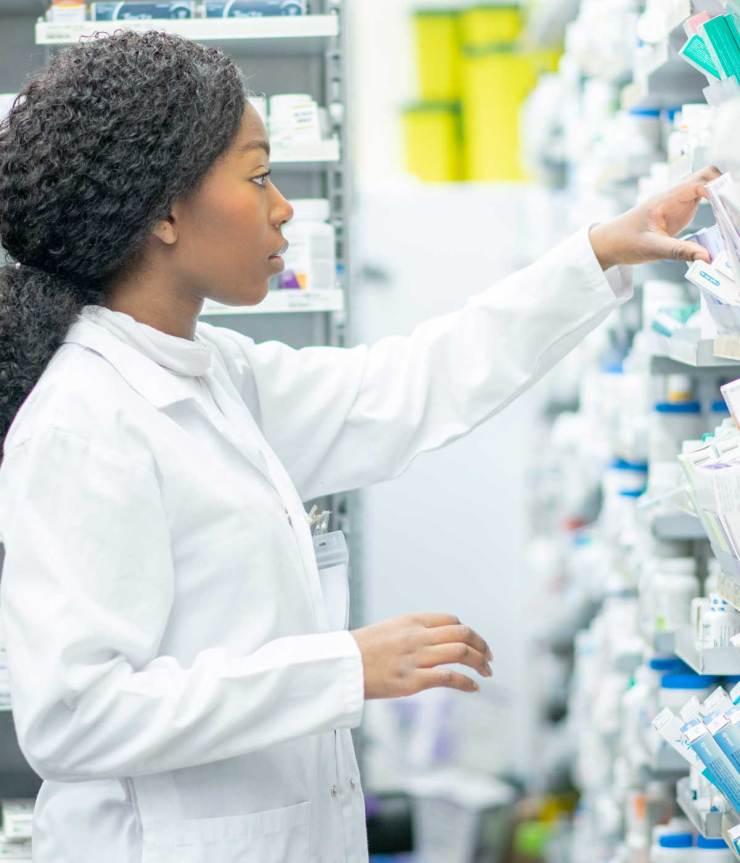 A female international student pharmacist in training reaches up into a shelf of prescription medicine