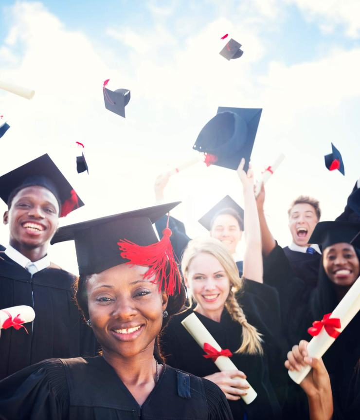 A group of smiling graduates in caps and gowns holding their diplomas