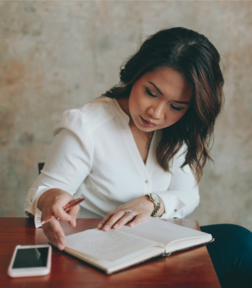 woman-sits-at-desk-writes-list
