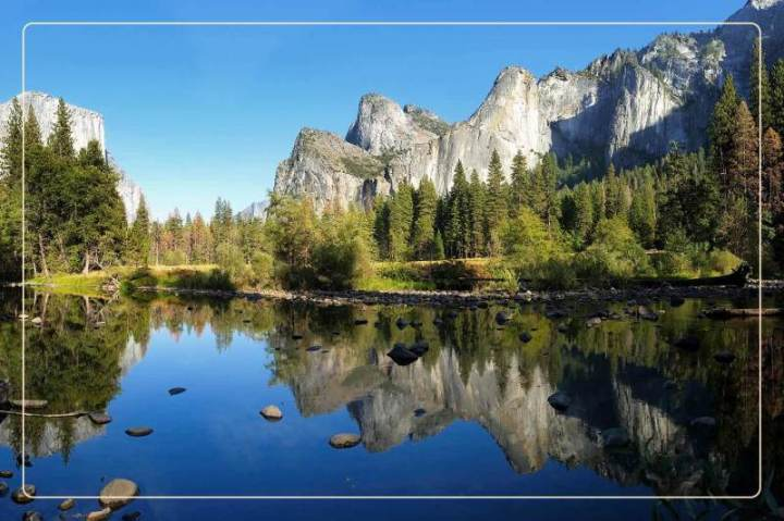 a body of water below a mountain range in Yosemite National Park, a dog-friendly national park where one can go hiking with dogs
